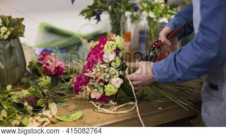 Close Up Male Florist Creating Flower Bouquet Flower Shop. High Quality And Resolution Beautiful Pho