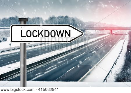 Lockdown - Sign With Text Lockdown In Front Of An Empty German Highway In Winter - Snow Covered. Emp