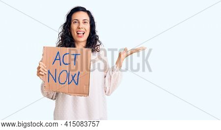Young beautiful hispanic woman holding act now banner celebrating victory with happy smile and winner expression with raised hands