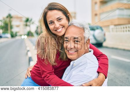 Middle age hispanic couple smiling happy and hugging sitting on the bench.