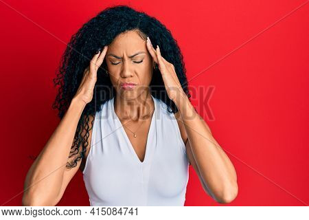 Middle age african american woman wearing casual white t shirt with hand on head, headache because stress. suffering migraine.
