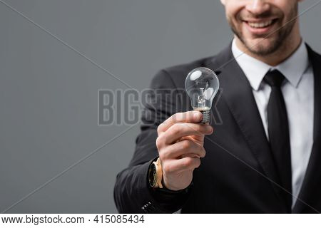 Cropped View Of Smiling Businessman Showing Light Bulb On Blurred Background Isolated On Grey.