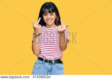 Young hispanic girl wearing casual clothes showing middle finger doing fuck you bad expression, provocation and rude attitude. screaming excited