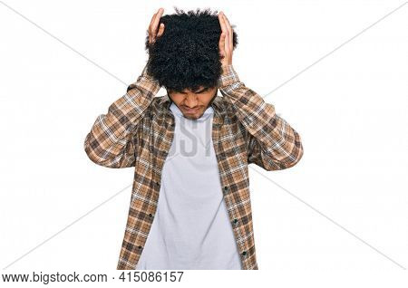 Young african american man with afro hair wearing casual clothes suffering from headache desperate and stressed because pain and migraine. hands on head.