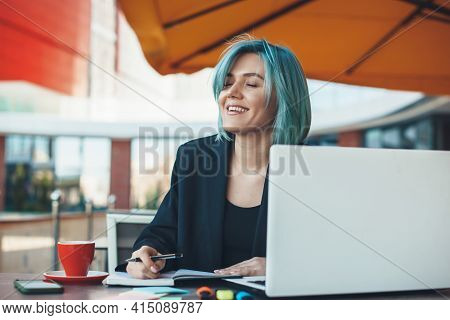 Blue Haired Caucasian Businesswoman Is Smiling In A Cafeteria Drinking A Tea And Working At The Lapt
