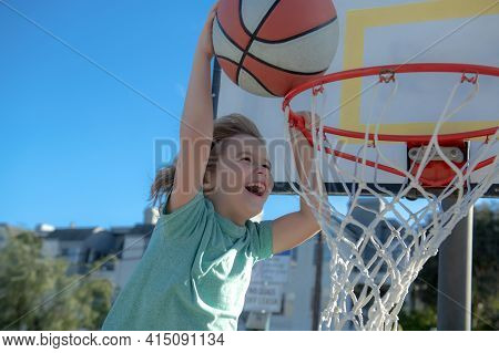 Close Up Image Of Basketball Excited Kid Player Dunking The Ball, Outdoor On Playground. Child Scori