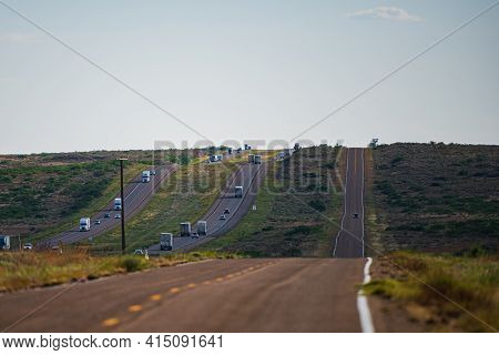 American View Of An Endless Straight Road Running Through The Barren Scenery Of The Southwest