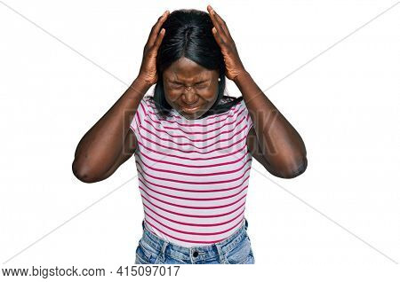 African young woman wearing casual striped t shirt suffering from headache desperate and stressed because pain and migraine. hands on head.