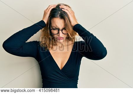 Young caucasian woman wearing business shirt and glasses suffering from headache desperate and stressed because pain and migraine. hands on head.
