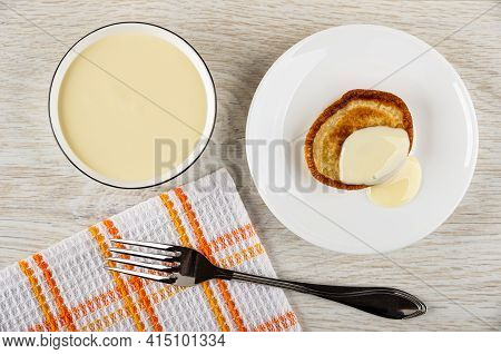 Bowl With Condensed Milk, Pancake Poured Condensed Milk In White Saucer, Fork On Checkered Napkin On