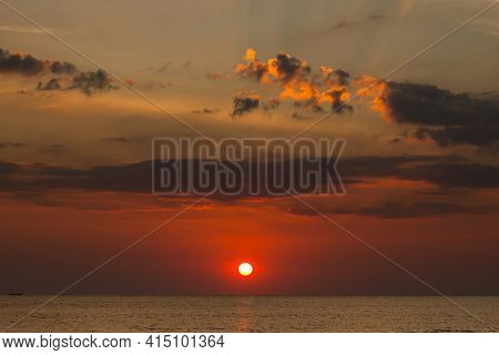 Big Sun Setting Down Over The Sea, The Red Disc Of The Sun Touches The Horizon In The Ocean.