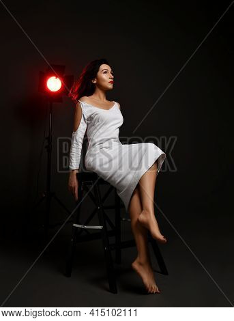 Sensual Pretty Woman Actress In White Dress Sits Barefooted On Chair In Neon Spotlight Glow And Look