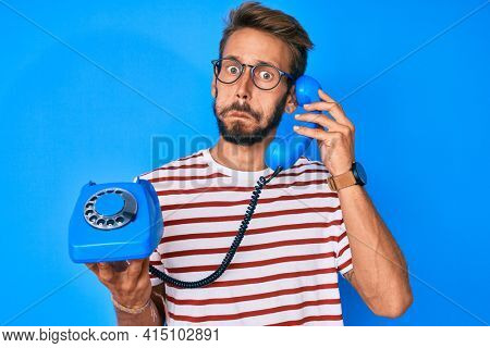 Handsome caucasian man with beard holding vintage telephone puffing cheeks with funny face. mouth inflated with air, catching air.