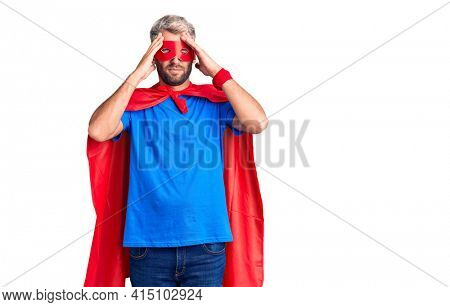 Young blond man wearing super hero custome with hand on head for pain in head because stress. suffering migraine.