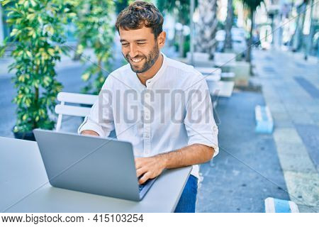 Handsome man with beard wearing casual white shirt on a sunny day working using laptop at cafeteria