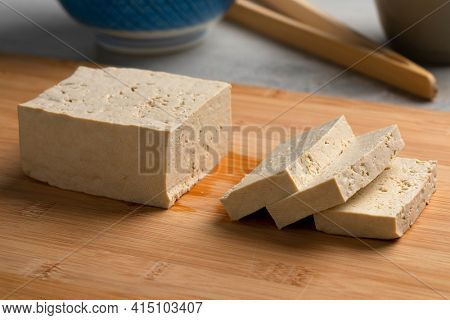 Piece of fresh raw organic tofu and slices on a cutting board close up