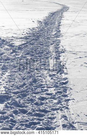 A Trodden Path Along The Surface Of A Frozen River.