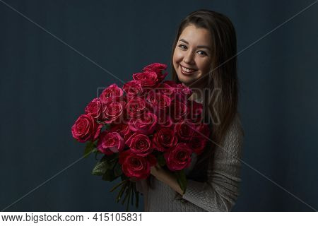 Young Woman Holding Bouquet Of Roses Flowers
