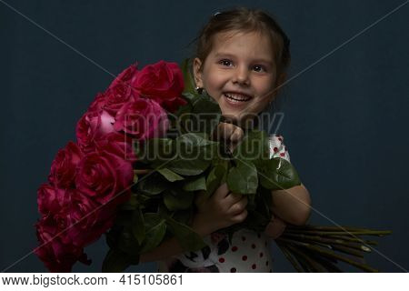 Little Girl With A Flowers Bouquet. Cute Baby Girl With Bouquet Of Roses Flowers On Dark Background