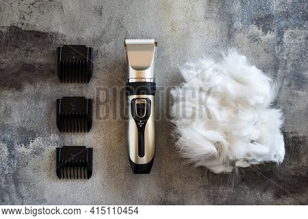 Grooming Tool. Hair Trimmer And Cat Or Dog Wool Lying On Concrete Background. Pet Care At Home. Remo