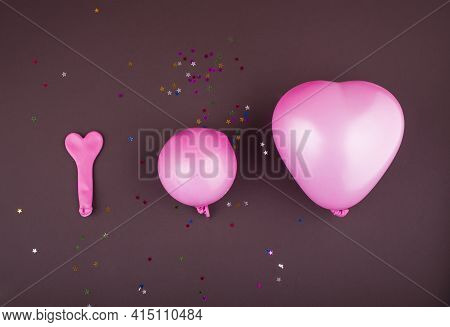 Three Pink Balloons For Helium And Air In The Shape Of A Heart Of Different Sizes On A Brown Backgro