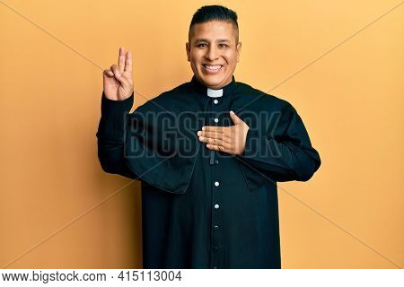 Young latin priest man standing over yellow background smiling swearing with hand on chest and fingers up, making a loyalty promise oath