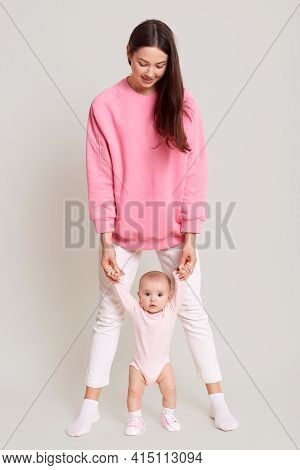 Mother Teaching Her Little Baby To Walk Isolated Over White Background, Dark Haired Woman Wearing Wh