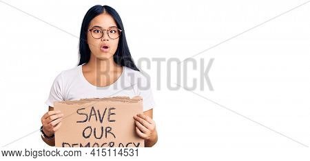 Young beautiful asian girl holding save our democracy protest banner scared and amazed with open mouth for surprise, disbelief face
