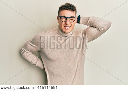 Hispanic young man wearing casual turtleneck sweater suffering of neck ache injury, touching neck with hand, muscular pain