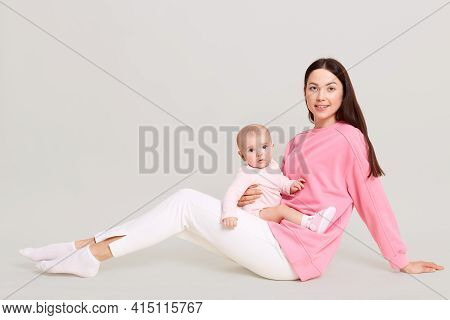 Young European Mom Sitting On Floor With Her Little Daughter In Her Arms, Baby In Bodysuit On Mother
