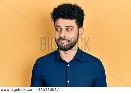 Young arab man with beard wearing casual shirt smiling looking to the side and staring away thinking.