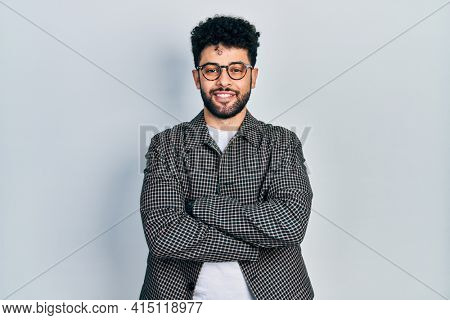 Young arab man with beard wearing glasses happy face smiling with crossed arms looking at the camera. positive person.