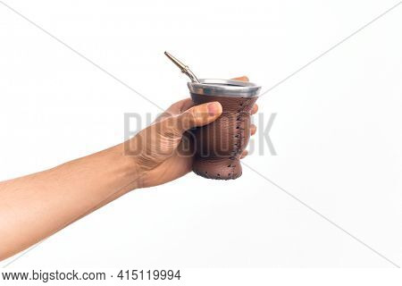 Hand of caucasian young man holding cup of mate infusion beverage over isolated white background