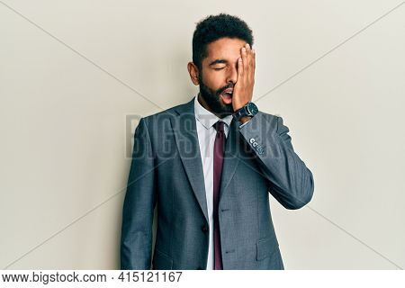 Handsome hispanic man with beard wearing business suit and tie yawning tired covering half face, eye and mouth with hand. face hurts in pain.