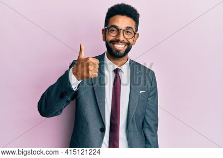 Handsome hispanic business man with beard wearing business suit and tie doing happy thumbs up gesture with hand. approving expression looking at the camera showing success.