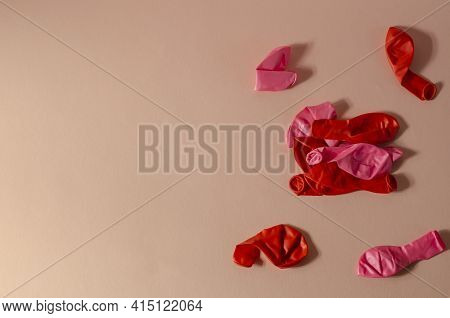 Minimalistic Composition With Deflated Balloons On A Pink Background. Several New Red And Pink Ballo