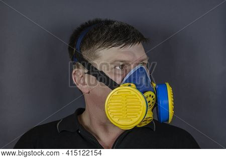 Portrait Of A Man In An Industrial Respirator On A Gray Background. An Adult Male With Short Hair We