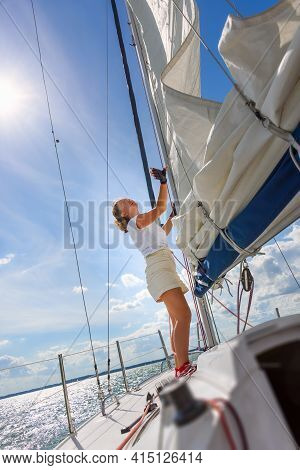 Young Woman Sailing On A Yacht. Female Sailboat Crewmember Trimming Main Sail During Sail On Vacatio