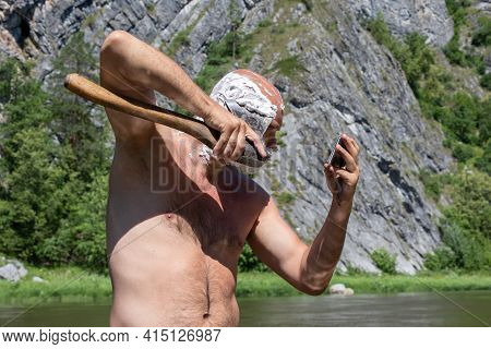 Naked Bold Man Chaves Cheek Axe Looking At Phone On Natural Background. Morning On Hike.