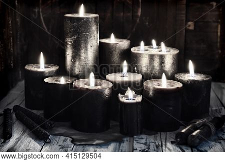 Group Of Black Burning Candles On Witch Table, Grunge Style.  Esoteric, Gothic And Occult Background