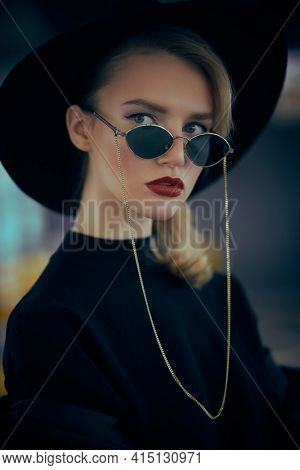 Close-up portrait of a fashionable young woman in modern sunglasses and hat in interiors. Beauty, fashion concept. Optics, eyewear. Copy space.