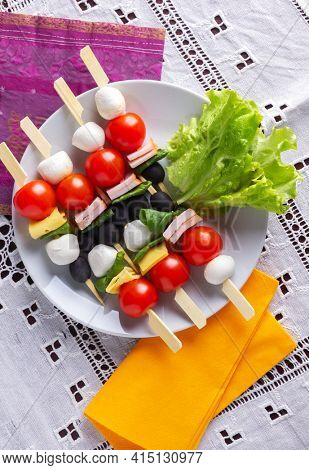Antipasti on bamboo skewers with mozzarella, cherry tomatoes, ham, cheese, spinach and black olives. Top view.