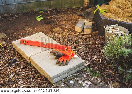 Building garden path or base in garden, spirit level, working gloves and concrete slabs