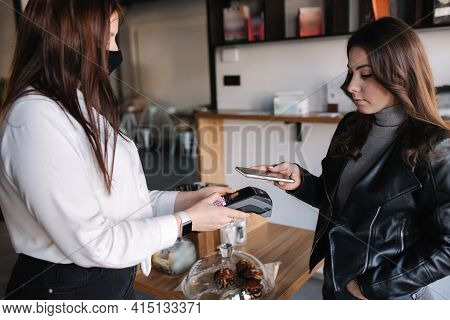 Young Woman Paying Bill Through Smartphone Using Nfc Technology In A Cafe. Female Customer Paying Us