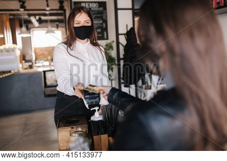 Female Customer Making Wireless Or Contactless Payment Using Credit Card. Cashier In Focus. Store Wo