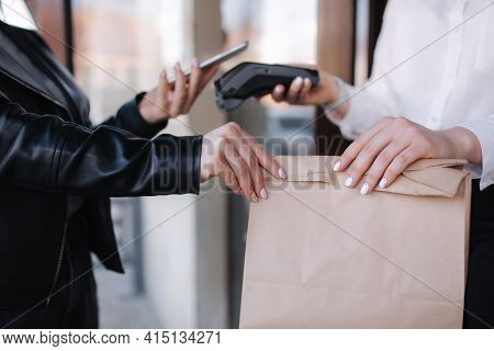 Closeup Of Female Standing Outdoors By Cafe And Paying With Smartphone During Covid-19 Pandemic. Cas