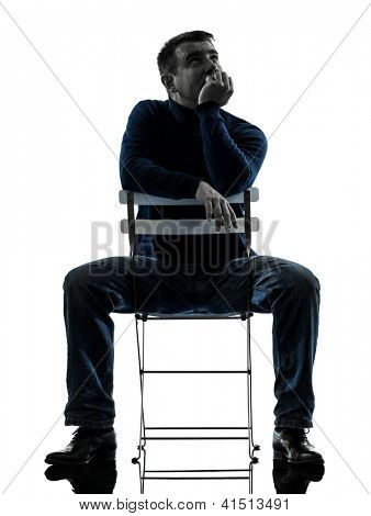 one caucasian man sitting  thinking pensive  full length in silhouette studio isolated on white background