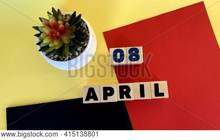 April 8 On Wooden Cubes.next To It Is A Potted Cactus On A Multicolored Red Yellow Black Background.