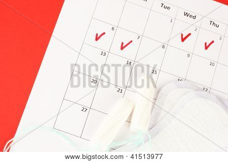 menstruation calendar with sanitary pads and tampons, close-up