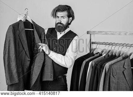 Man In Custom Tailored Suit Presenting Tailored Tuxedo. Man Clothing In Boutique. Tailor In His Work